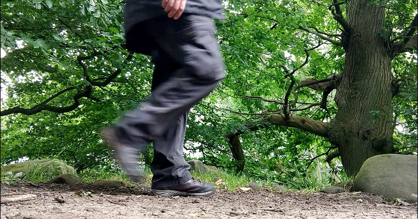 person on path in wood in mid step, right leg blurred